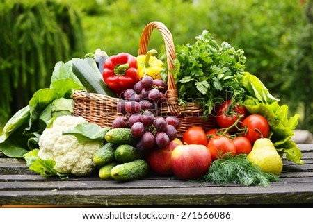 Fresh organic vegetables in wicker basket in the garden - stock photo
