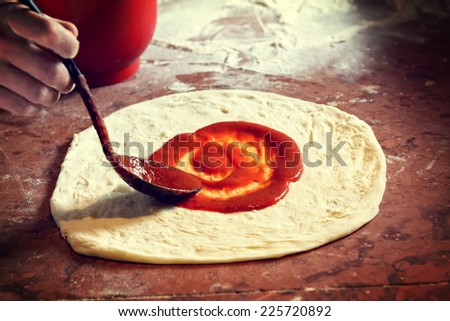 Fresh original Italian raw pizza, dough preparation in traditional style. Applying a tomato sauce. - stock photo