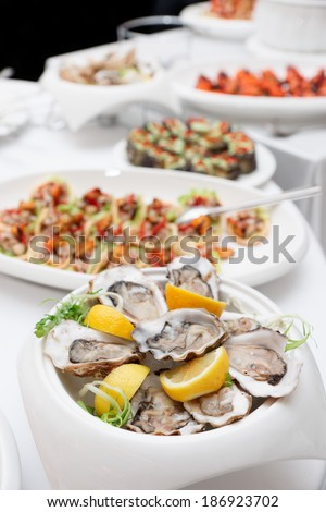 Fresh oysters and snacks on restaurant table - stock photo