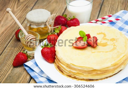 Fresh pancakes in a plate with strawberries,milk and honey on a wooden background
