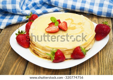 Fresh pancakes in a plate with strawberries on a wooden background