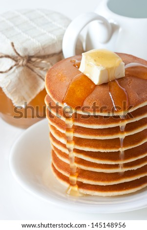 Fresh pancakes with butter and honey on a plate. - stock photo
