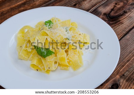 Fresh pappadelle pasta with lemon, basil and creame with parmesan - stock photo