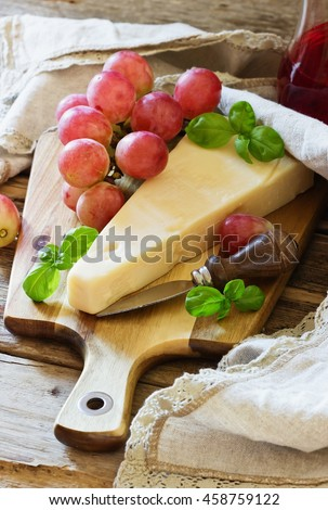 Fresh parmesan cheese and ripe grapes on a table. Health and diet food. Selective focus - stock photo
