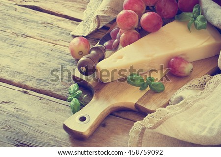 Fresh parmesan cheese and ripe grapes on a table. Tinted image. Health and diet food. Selective focus - stock photo