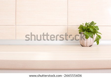 Fresh parsley in pot on wooden kitchen countertop - stock photo