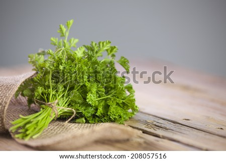 fresh parsley on wooden table - stock photo