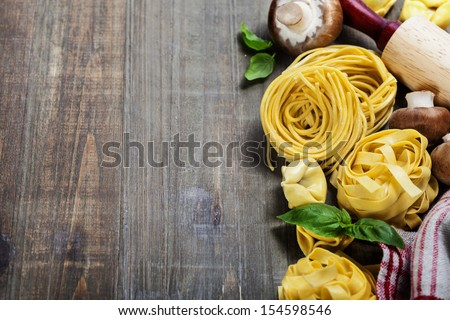 Fresh pasta and italian ingredients on wooden table - stock photo