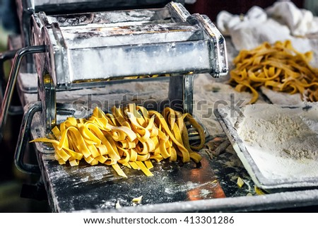 Fresh pasta and pasta machine on kitchen table. Fettuccine homemade. Process of making homemade pasta linguine, closeup. - stock photo