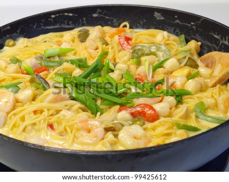 Fresh Pasta and Seafood in a Cream Sauce Garnished with Green Onions - stock photo