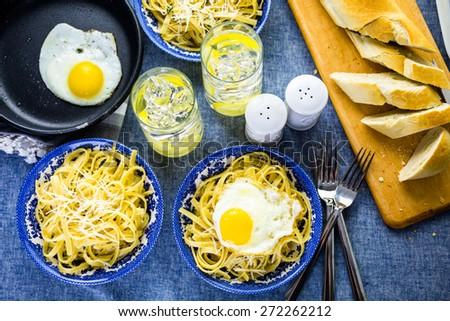Fresh pasta pangrattato with crispy eggs on the table. - stock photo
