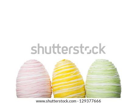 Fresh pastel handcrafted Easter Eggs covered in raffia or coloured straw standing in a row against a white background with copy space for your seasonal greeting