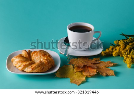 Fresh pastry roll and flowers on aquamarine shadowless background