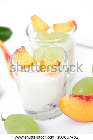 Fresh peach and grape yogurt in glass - stock photo