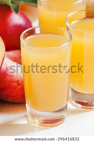 Fresh peach juice with fruits on a white wooden background, selective focus