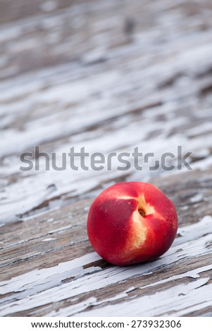 fresh peach on a wooden table with flaking paint copy space - stock photo