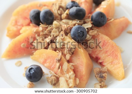 Fresh peach slices and blueberries sprinkled with granola - stock photo