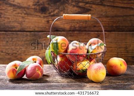 fresh peaches in a basket on wooden table - stock photo