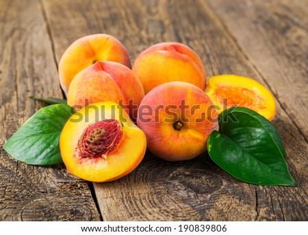 fresh peaches on wood background - stock photo