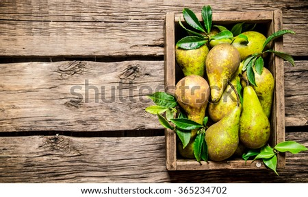 Fresh pears in an old box with leaves. On wooden background. Free space for text . Top view - stock photo