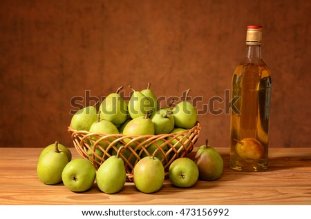 Fresh pears in wicker basket and a bottle of brandy on the table