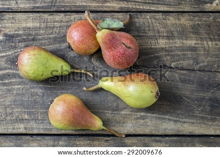 Fresh pears on dark wooden table. - stock photo