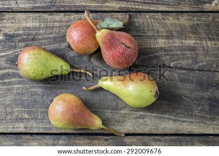 Fresh pears on dark wooden table. - stock photo