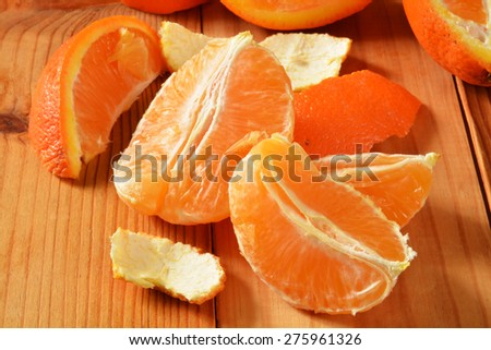 Fresh peeled and separated orange wedges on a rustic wooden table - stock photo