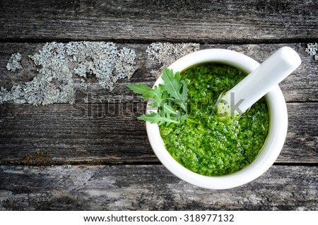 Fresh pesto of rucola in white pounder on vintage wooden background