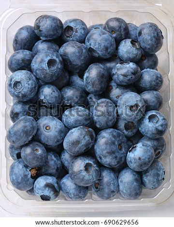 Fresh picked blueberries in clear plastic container in vertical format.  Shot from overhead.
