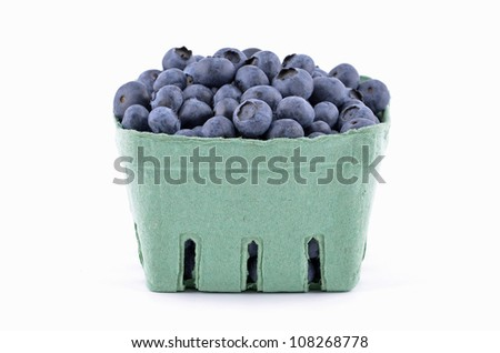 Fresh picked blueberries in green cardboard basket on white background