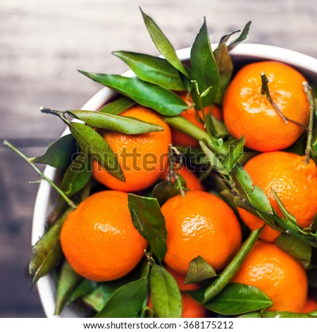 Fresh picked tangerine clementines in white bowl with copy space, top view image - stock photo