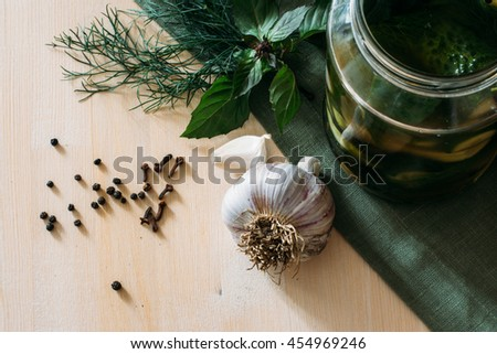 fresh pickled cucumbers in jar with herbs on rustic wooden surface - stock photo