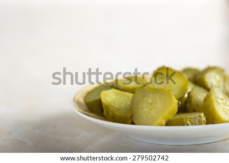Fresh pickles slices on a small plate - stock photo