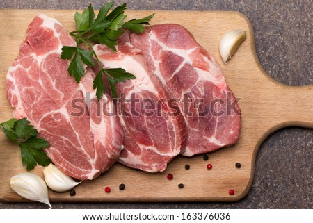 fresh pieces of meat with garlic, pepper and parsley - stock photo