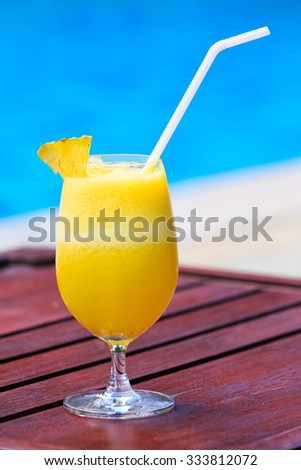 Fresh pineapple juice cocktail near the swimming pool - stock photo