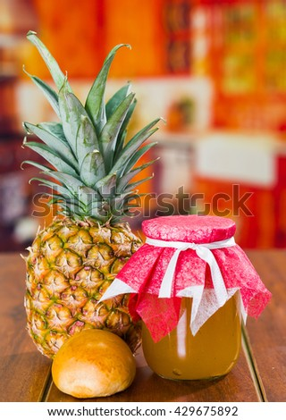 Fresh pineapple on a wooden table with a little bread and a glass pot, homemade - stock photo