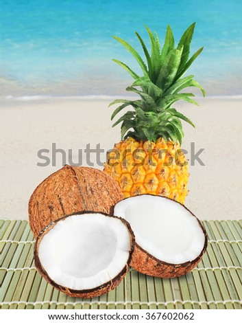 Fresh pineapple with green leaves and two halves of brown coconut. Beach, sand and blue ocean on background. - stock photo
