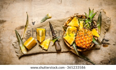 Fresh pineapples, whole and sliced in a basket on old fabric. On a wooden table. Top view - stock photo
