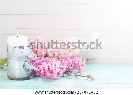 Fresh pink hyacinths  and  candle in ray of light  on  turquoise painted wooden planks against white wall. Selective focus. Place for text. - stock photo