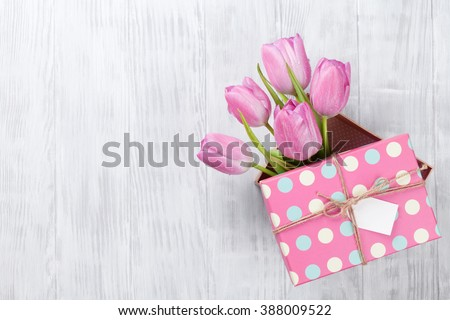 Fresh pink tulip flowers in gift box on wooden table. Top view with copy space - stock photo