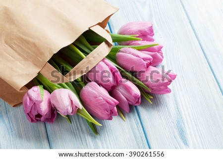 Fresh pink tulip flowers in paper bag on wooden table