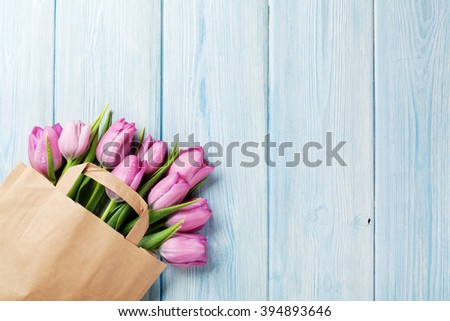 Fresh pink tulip flowers in paper bag on wooden table. Top view with copy space - stock photo