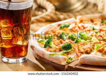 Fresh pizza with broccoli and chicken served with cold cola - stock photo