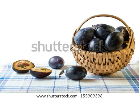 Fresh plums in basket - stock photo