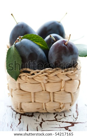 fresh plums in the basket - stock photo