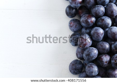 Fresh plums on the white wooden background - stock photo