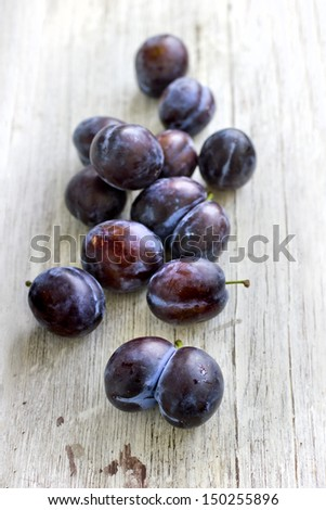 Fresh plums on white wooden background - stock photo