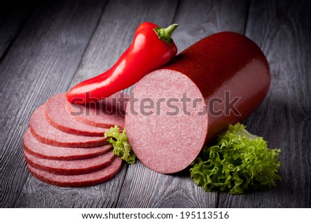 Fresh polish salami sausage slices. Meat composition taken on rustic wooden table. - stock photo