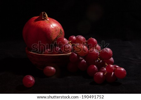 Fresh pomegranate and grapes on black background. - stock photo